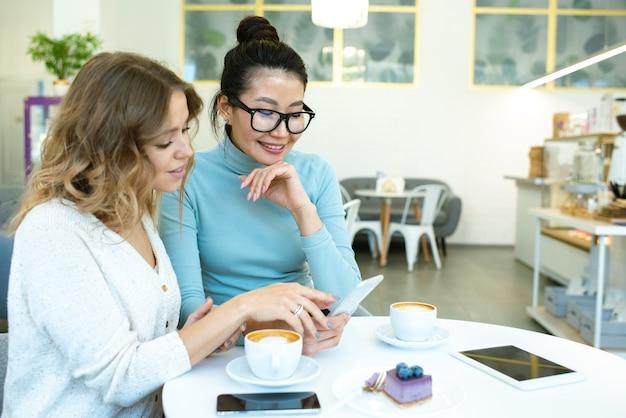 Две спокойные межкультурные девушки выбирают товары в интернет-магазине, прокручивая смартфон за столиком в кафе