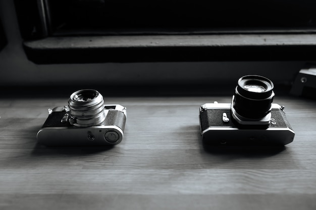 Two retro film cameras lie on a wooden table. black and white