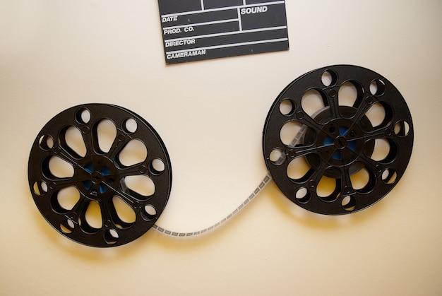 壁にカチンコが付いている2つのレトロな映画フィルムリール