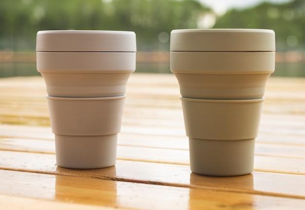 自然の中で木製のテーブルに2つの再利用可能なエコカップ。持続可能なライフスタイルとゼロウェイストのコンセプト。
