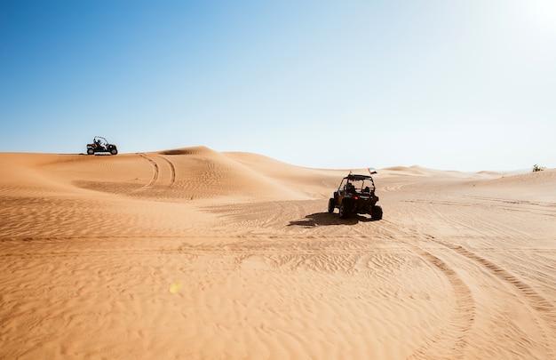 Two riding quad buggy bikes at al awir arabic desert sand hills, extreme sports