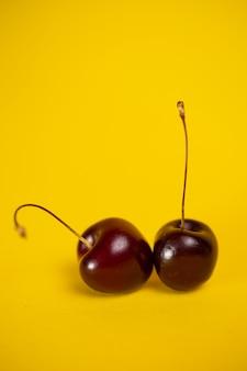 Две спелые вишни на желтом фоне.