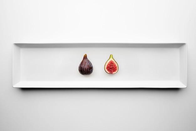 Два спелых свежих инжира, изолированные на центральной прямоугольной керамической тарелке на белом столе