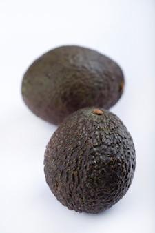 Два спелых здоровых авокадо, изолированные на белом фоне.