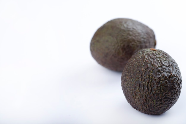 Two ripe healthy avocados isolated on white background.