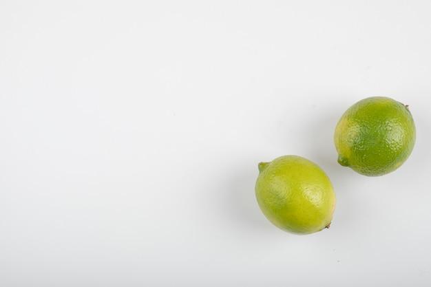 Due frutti di calce maturi isolati su priorità bassa bianca.
