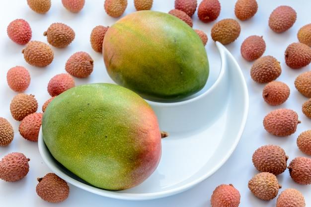 Два спелых манго в окружении спелых плодов личи на тарелке на белом фоне.
