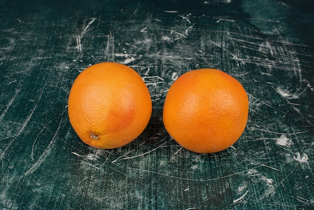 Two ripe oranges on marble surface.