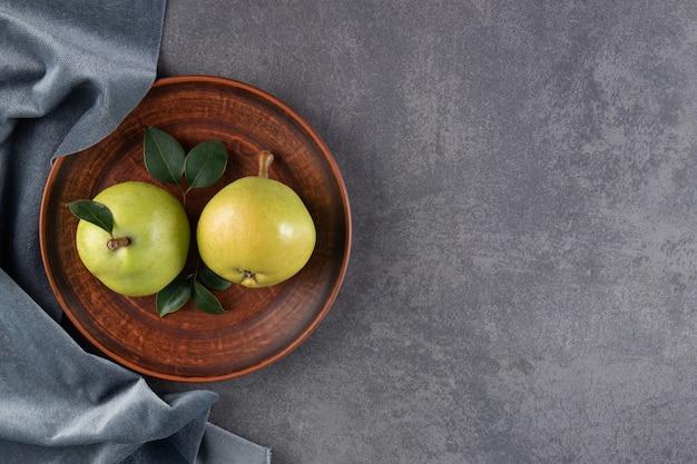 Due pere mature su un piatto e pezzi di tessuto, sul tavolo blu.