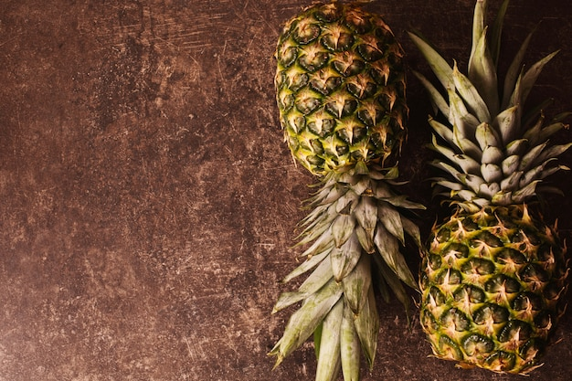 Two ripe pineapple lying on a dark marble table. delicious fruit. healthy eating.