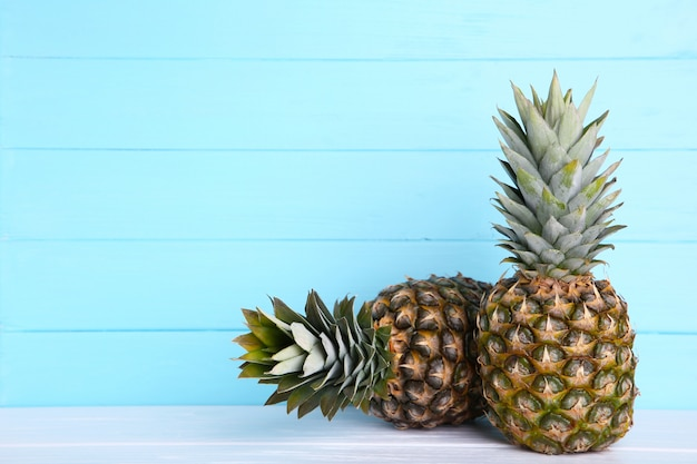 Two ripe pineapples on a blue background with copy space