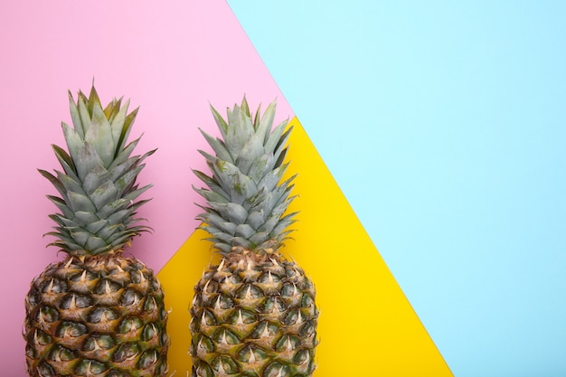 Two ripe pineapples on a colorful background