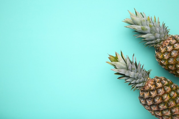 Two ripe pineapples on a mint background