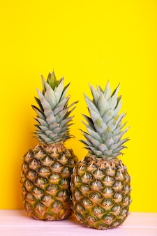 Two ripe pineapples on a yellow background