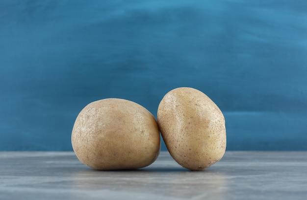 大理石のテーブルの上にある2つの熟したジャガイモ。