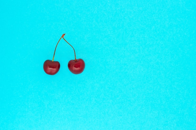 Two ripe red cherries on blue background