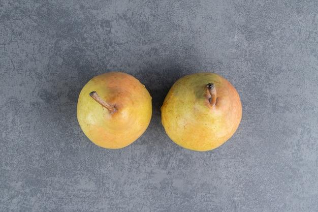 회색 표면에 고립 된 두 잘 익은 빨간색 노란색 배 과일