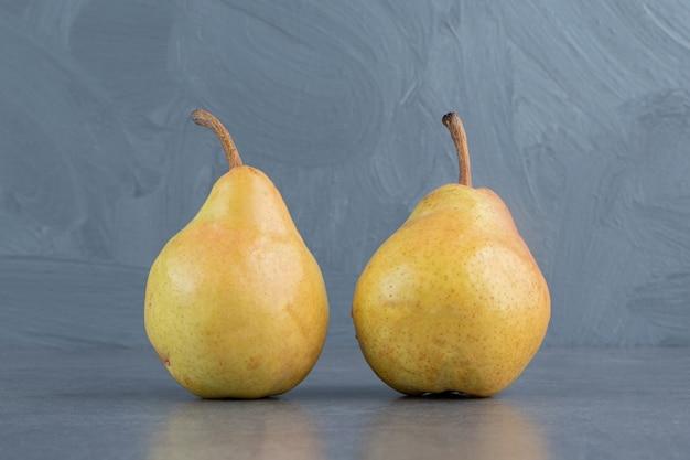Два спелых красных желтых плода груши, изолированные на серой поверхности