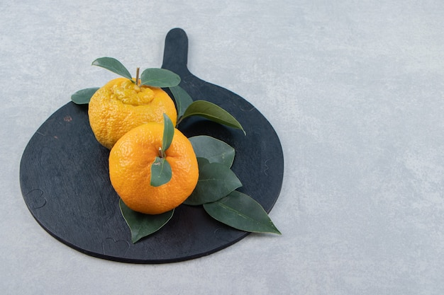 Due mandarini maturi con foglie su tagliere nero.