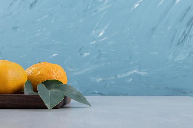 Два спелых мандарина с листьями на темной тарелке