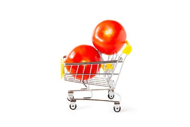 Два спелых помидора в маленькой игрушечной тележке на белом изолированном фоне.