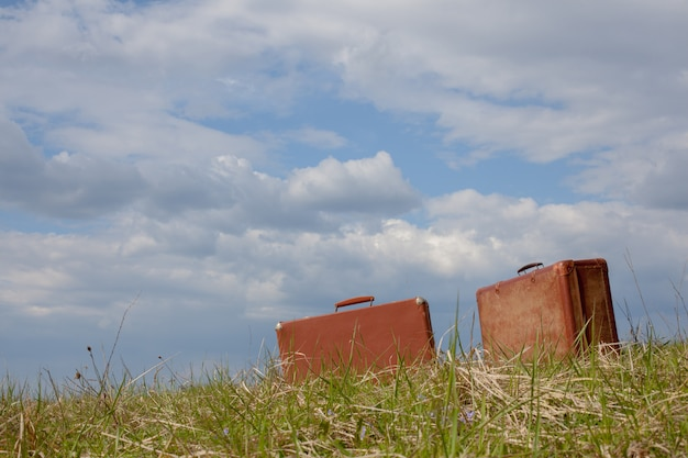 Two road brown suitcase sitting on the grass against the blue sky