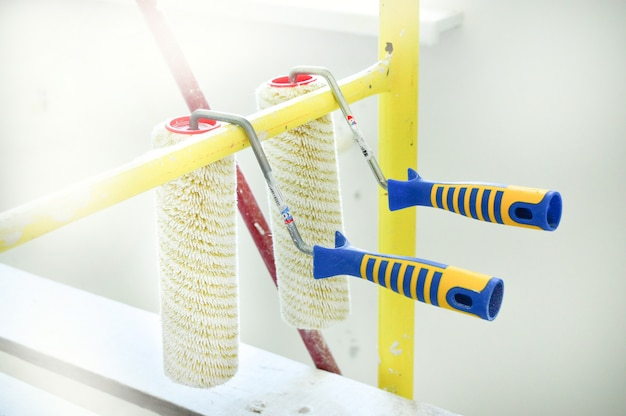 Two rollers for painting walls against background of apartment