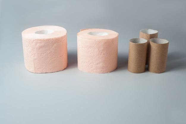 На сером фоне стоят два рулона розовой туалетной бумаги и несколько рукавов от них.