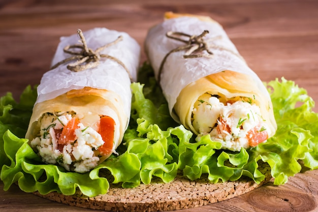Two rolls of pita stuffed with cheese, chicken and tomatoes lay on the lettuce