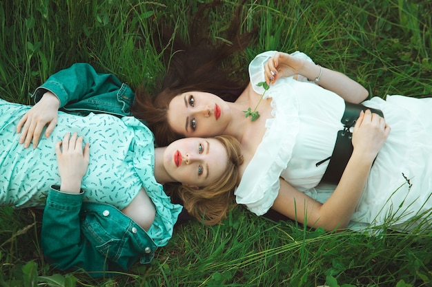 잔디 풀밭에 누워 두 로맨틱 소녀입니다. 평면도. 소프트 포커스. 자유와 젊음의 개념