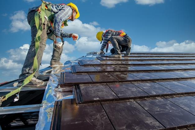 Два кровельщика в защитной одежде работают в команде, чтобы установить крышу дома, крыша из керамической черепицы на строительной площадке.