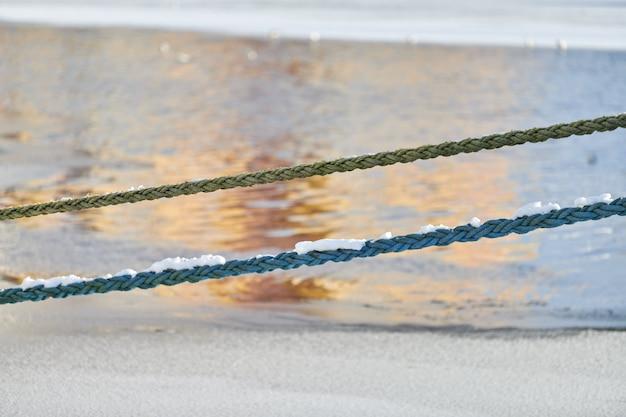 Две веревки на фоне морской воды зимой. веревки, свисающие с рыбацкого корабля или яхты, крупным планом.