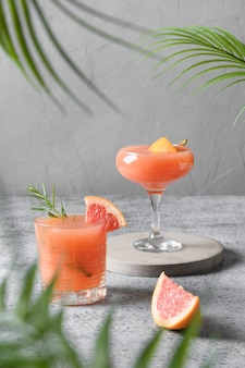 Две газированные напитки грейпфрута розмарина на сером.