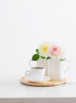 Две розы в чашках с чашкой кофе