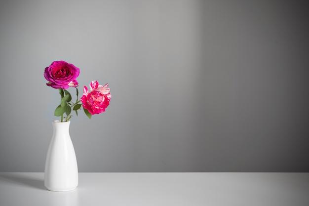 회색 배경에 꽃병에 두 개의 장미