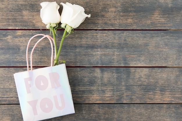 Due rose in sacchetto di carta con per te iscrizione