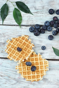 Two round waffles on a light wooden table and blueberries