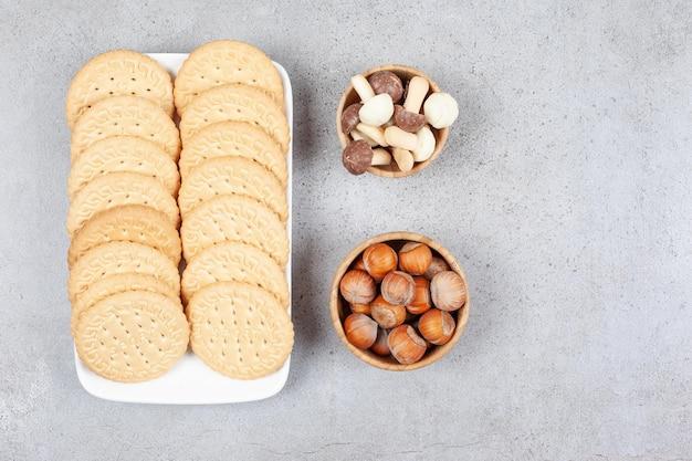 Два ряда печенья на блюде рядом с небольшими мисками с шоколадными грибами и фундуком на мраморном фоне. фото высокого качества
