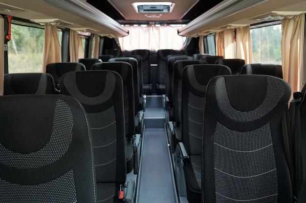 Два ряда серых и черных двухместных сидений внутри автобуса