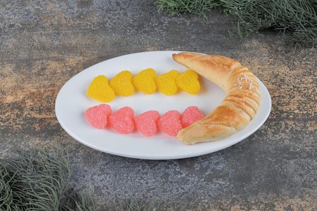 Два ряда мармеладов и булочка в виде полумесяца на блюде между ветками сосны на деревянной поверхности