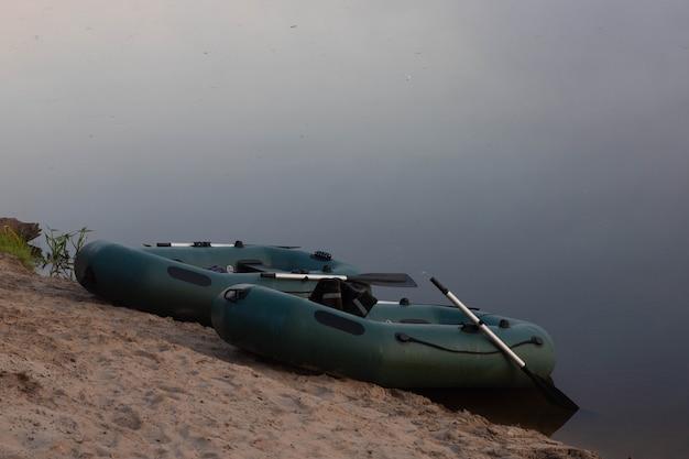 霧の中の早朝に釣り道具を持った2隻のゴムボートが川のほとりに駐車した。