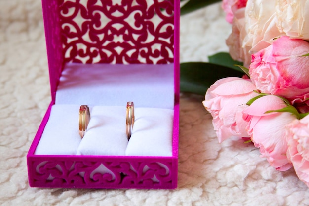 Two rustic wedding bouquet and rings in the box on a luxury sofa