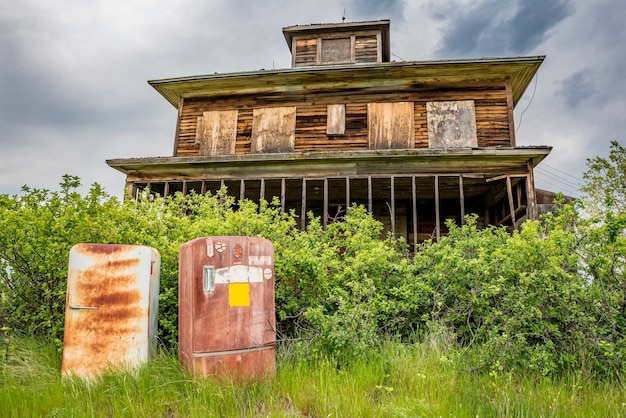 Two rusty vintage fridges abandoned outside an old home on the prairies