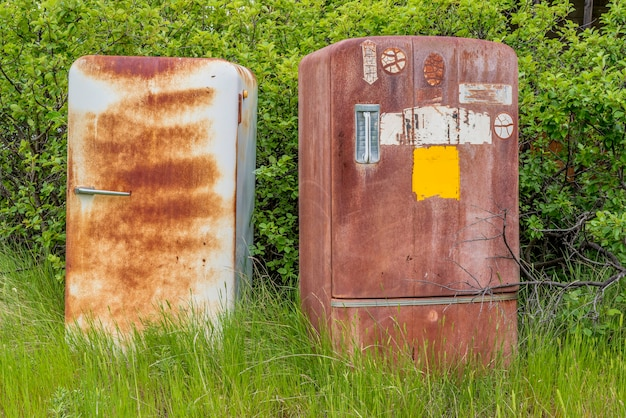 Two rusty vintage fridges abandoned on the prairies
