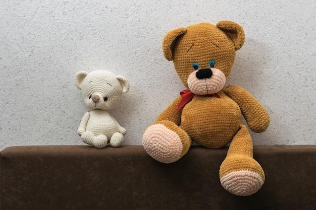 Два грустных вязаных медвежонка на диване у светлой стены. красивая вязаная игрушка.