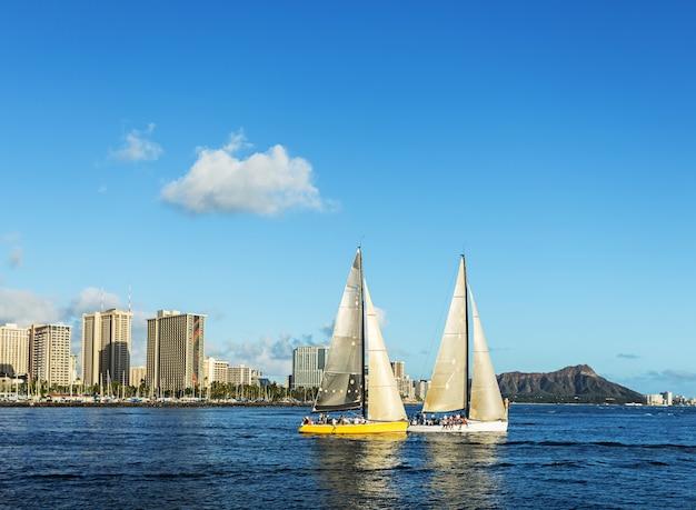 ダイヤモンドヘッド山を背景に、ハワイのホノルルの海で2つのヨット