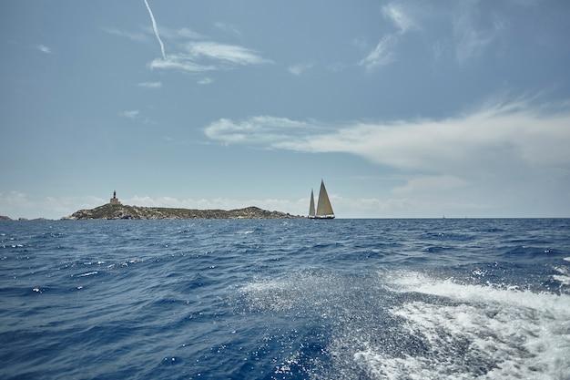 壮大な風景の前で2隻の帆船が海を航行します