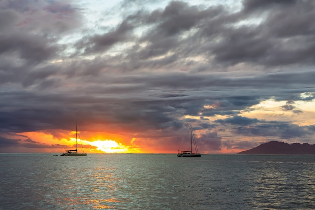 Two sailing boats over dark clouds surface and orange sunset sea