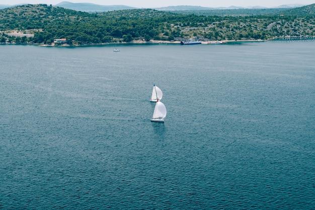 帆を膨らませた2隻のセーリングヨットが海岸を背景に海を航行します