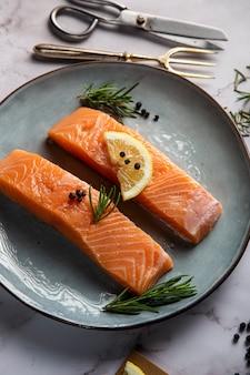 Два филе лосося с лимоном веточка розмарина и перца